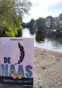 Een kaart met daarop het logo van De Naas en de tekst Applaus veur dich staat op de Stenen Brug in Roermond. De A in Naas lijkt een bos bloemen vast te hebben. Op de achtergrond een mooi uitzicht op de Roer.